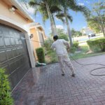Hispanic male power washing an upscale home before painting in a 55+ senior gated community. Taken with a Canon 5D Mark IV.
