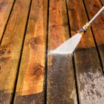 """A pressure washer sprayer is cleaning a weathered treated wood deck. The background area has been cleaned, the lower portion is dirty and weathered, showing the contrast."""