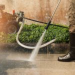 Worker cleaning driveway with gasoline high pressure washer ,professional cleaning services.